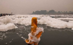 Foam from industrial runoff drifts past worshipers in the Yamuna River in New Delhi, Nov 2, 2019. The New York Times