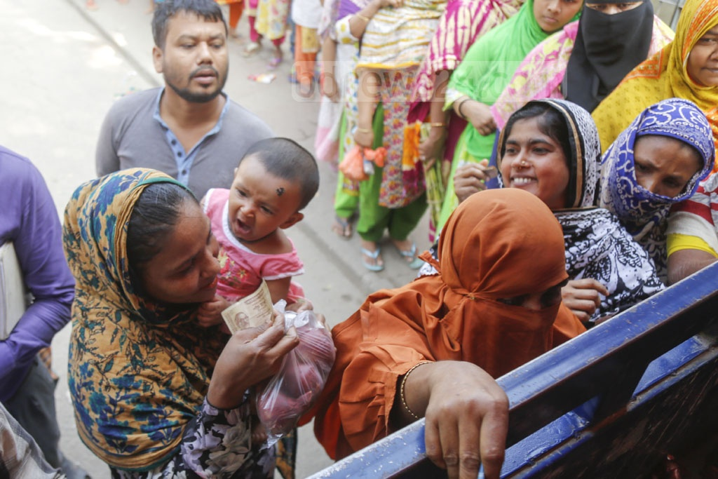 A woman secures onion after waiting in queues with her baby in the lap for a long time. Photo: Mahmud Zaman Ovi