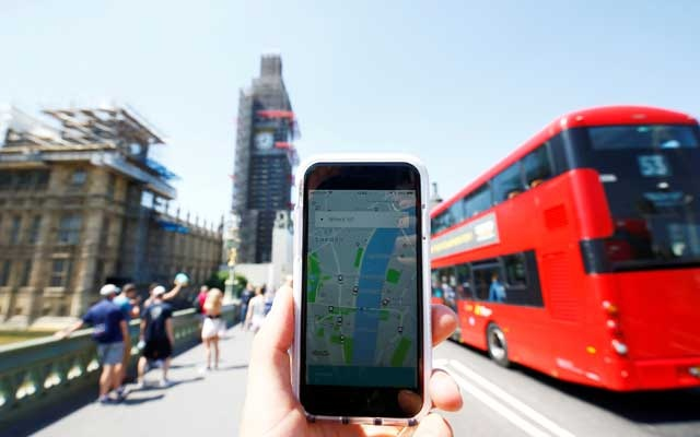 FILE PHOTO: A photo illustration shows the Uber app and a bus in London, Britain, Jun 25, 2018. REUTERS