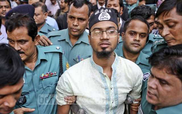 Police escorting Rakibul Hasan Regan, an operative of neo-JMB wearing a prayer cap emblazoned with the Islamic State's insignia, after a Dhaka tribunal announced the verdict on Holey Artisan Bakery attack case on Wednesday.