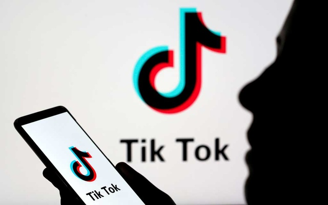 A person holds a smartphone as Tik Tok logo is displayed behind in this picture illustration taken Nov 7, 2019. Reuters