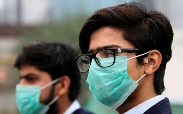 FILE PHOTO: Men wearing protective masks wait for a bus in Lahore, Pakistan Nov 22, 2019. REUTERS