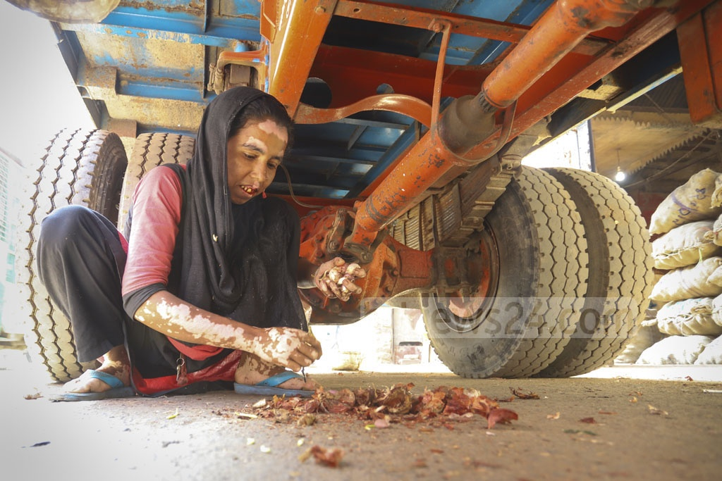 A woman collecting dumped onion from under a truck at Shyambazar wholesale market in Dhaka on Friday. Photo: Asif Mahmud Ove