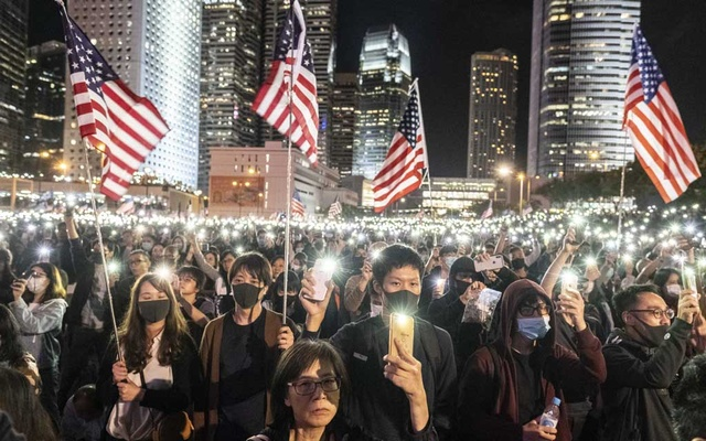Demonstrators wave US flags during a protest in Hong Kong on Thursday, Nov 28, 2109.