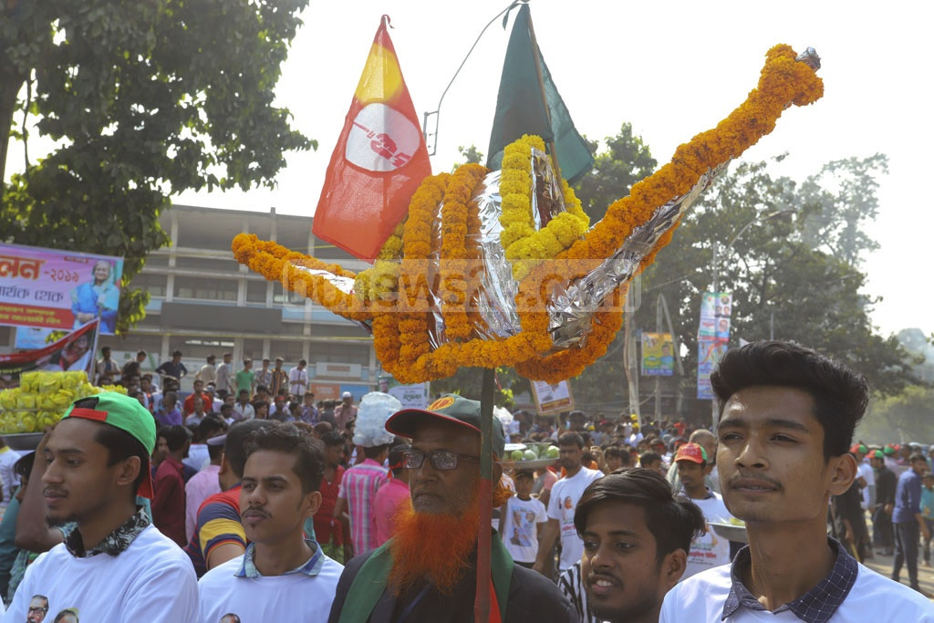 Awami League activists carrying replicas of the party's electoral symbol boat march toward the Suhrawardy Udyan in the capital to attend the council of the party's Dhaka South and North units on Saturday. Photo: Asif Mahmud Ove