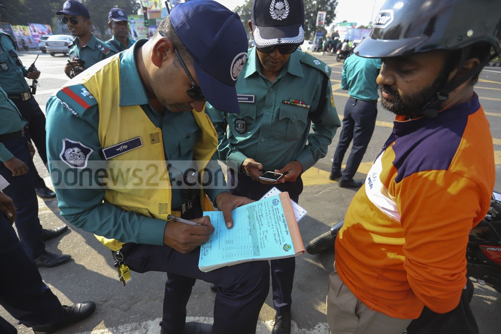 Police fine drivers for serious breach of the new Road Transport Act besides raising awareness among the drivers as part of a fortnightly campaign on Bijoy Sarani on Saturday. Photo: Asif Mahmud Ove