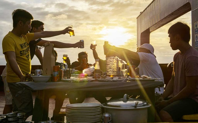 Crewmen raise a toast over barbecue aboard the UBC Cyprus, bound for the Philippines with a load of cement, Jul 6, 2019. The New York Times