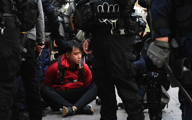 A protester is detained by riot police during the