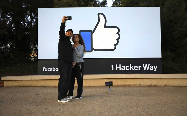 Visitors take a selfie by the Facebook sign at the company's campus in Menlo Park, Calif, Sept 18, 2019. The New York Times