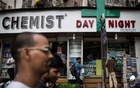 FILE PHOTO: People walk past a chemist shop at a market in Mumbai, India, Jun 24, 2014. REUTERS