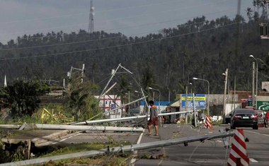 FILE PHOTO: A man walks past electric poles lying on the main highway after Typhoon Kammuri hit Camalig town, Philippines, Dec 3, 2019. REUTERS