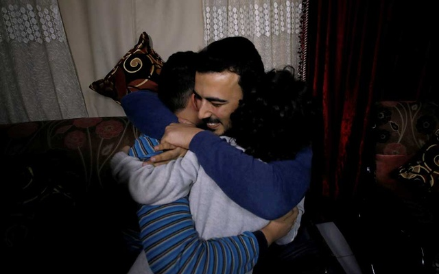 Palestinian journalist, Amjad Yaghi, hugs his younger brothers as he reunites with his mother after 20 years of separation, in Banha, Egypt December 2, 2019. Reuters
