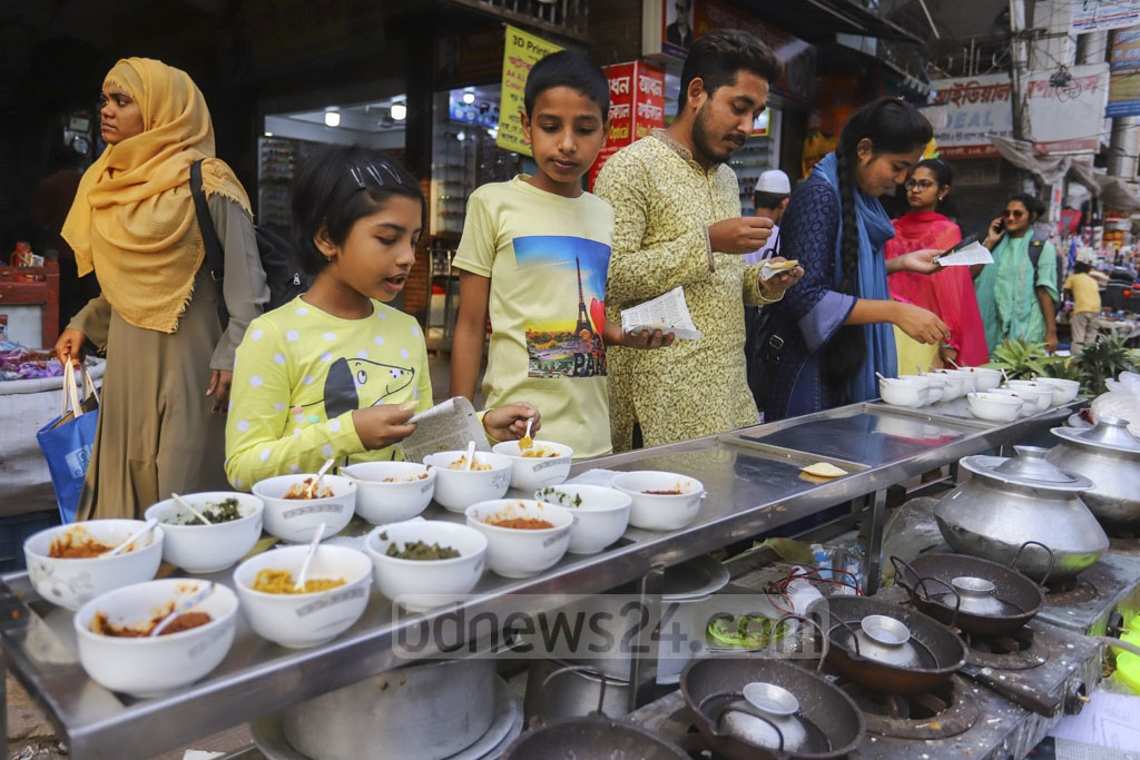 Customers of different ages savouring Chitai Pitha with Bharta in Dhaka's Farmgate. Photo: Asif Mahmud Ove