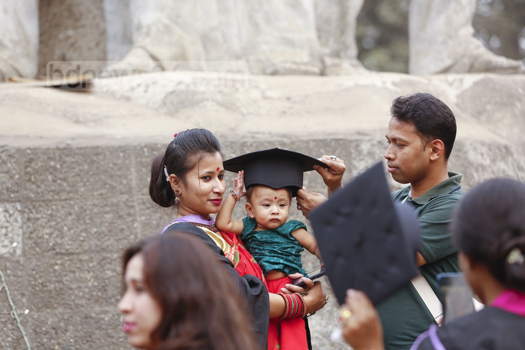A Dhaka University graduate putting her cap on her child's head at the TSC on Monday, the day of university's 52nd convocation. Photo: Mahmud Zaman Ovi