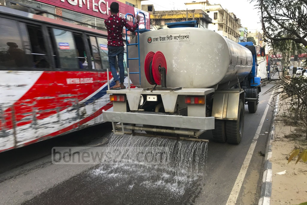 A city corporation vehicle sprays water on the street to remove dust at Rampura DIT Road in Dhaka on Tuesday.