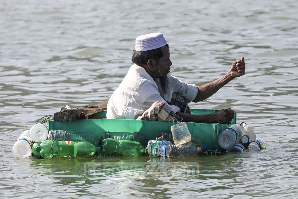 A fisherman climbs onto a raft made of plastic bottles to catch fish in the Naf River in Cox's Bazar. Photo: Mostafigur Rahman