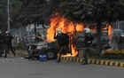 Police officers run past a vehicle on fire after a group of lawyers stormed the Punjab Institute of Cardiology (PIC) in Lahore, Pakistan December 11, 2019. REUTERS
