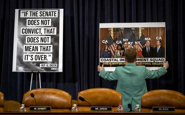 A House Republican staff member adjusts a poster before the start of a House Judiciary Committee markup session on the articles of impeachment against President Donald Trump in Washington on Thursday, Dec. 12, 2019. A somber but contentious debate is expected to culminate by the end of the day in a vote by the panel to send the charges to the full House. (Pete Marovich/The New York Times)