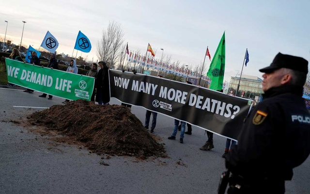 Climate change activists of Extinction Rebellion hold banners after unloading a truck filled with horse excrements in front of UN Climate Change Conference (COP25) in Madrid, Spain, December 14, 2019. Reuters