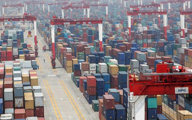 FILE PHOTO: A man walks in a shipping container area at Yangshan Port of Shanghai May 11, 2012. REUTERS