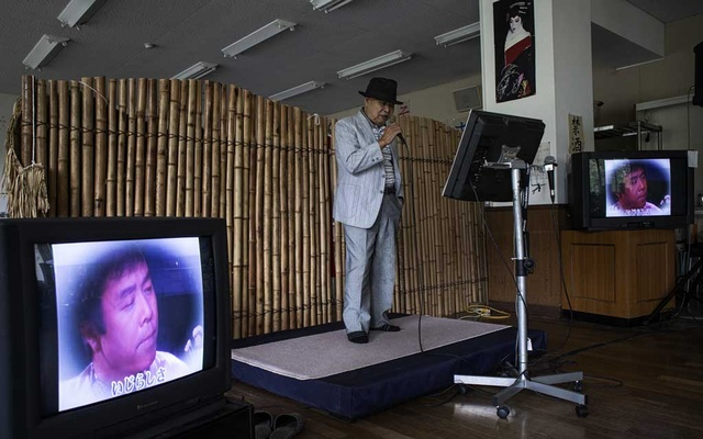 Mitsuhiro Uwaguri, 90, the village of Nagoro, Japan's oldest resident, sings karaoke with a group of friends, Oct 7, 2019. As the country's population shrinks and ages, rural areas are emptying out. The New York Times