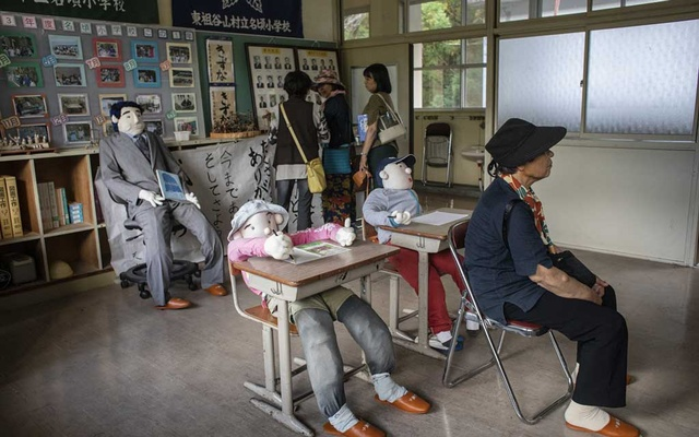 A group of women tour the school that was closed after the last two students, depicted as dolls, grew up, in Nagoro, Japan, Oct 4, 2019. In a childless mountain village on an island of Japan, two dozen adults compensate for the absence with the company of hundreds of giant handmade dolls. The New York Times