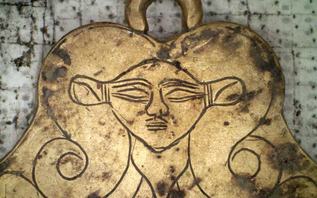 A photo provided by the University of Cincinnati shows a golden pendant depicting the head of the Egyptian goddess Hathor, found in a tomb at the site of the ancient city of Pylos in southern Greece. The discovery of this and other items suggest that Pylos, a city with a fine port, had trading connections, previously unknown, with Egypt and the Near East around 1500 BC, the time the tombs were in use. The New York Times