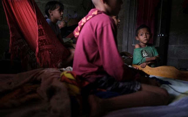 Jose Maria, 6, who is underweight for his age and has been diagnosed with malnutrition according to his mother Rosa Rojas, watches a neighbour play a video game at his house in Barquisimeto, Venezuela, Aug 15, 2019.