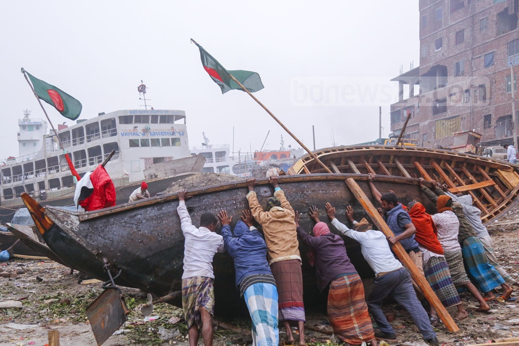 Workers repairing a boat on the dried up bank of the Buriganga at Telghat pier in Dhaka's Keraniganj on a winter afternoon. Photo: Mahmud Zaman Ovi