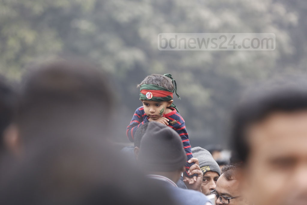 A man carrying his son on his shoulder, wades through the crowd outside the Suhrawardy Udyan ahead of the Awami League's 21st National Council on Friday. Photo: Mahmud Zaman Ovi