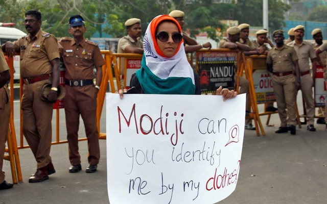 A demonstrator displays a placard as she attends a protest against a new citizenship law, in Chennai, India, December 20, 2019. REUTERS