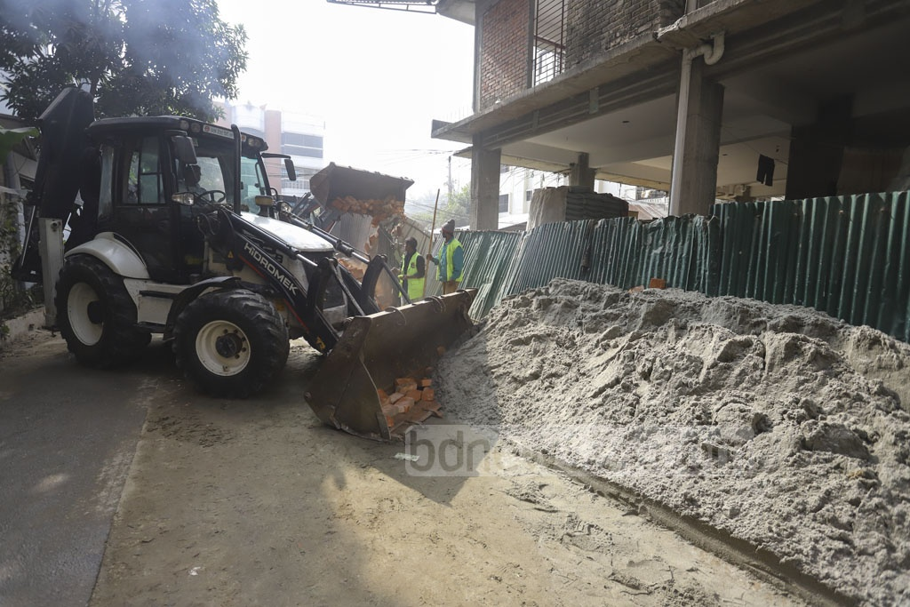 A mobile court, run by Dhaka North City Corporation, removes construction materials to free a road during a drive at the capital's Niketan on Tuesday. Photo: Asif Mahmud Ove