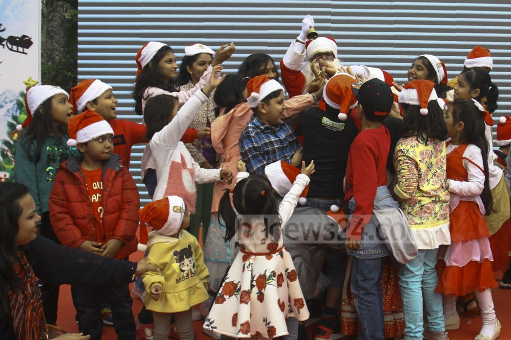 Santa Claus distributing gifts among children at the Pan Pacific Sonargaon Hotel in Dhaka during Christmas celebrations on Wednesday.