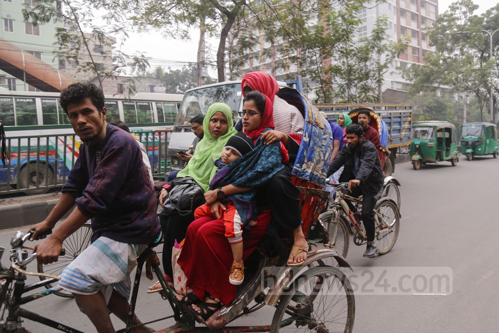 A woman holding a baby wrapped in clothes on a rickshaw as the residents of Dhaka try to keep themselves warm due to the chilly weather after mild overnight rains on Friday. Photo: Mahmud Zaman Ovi