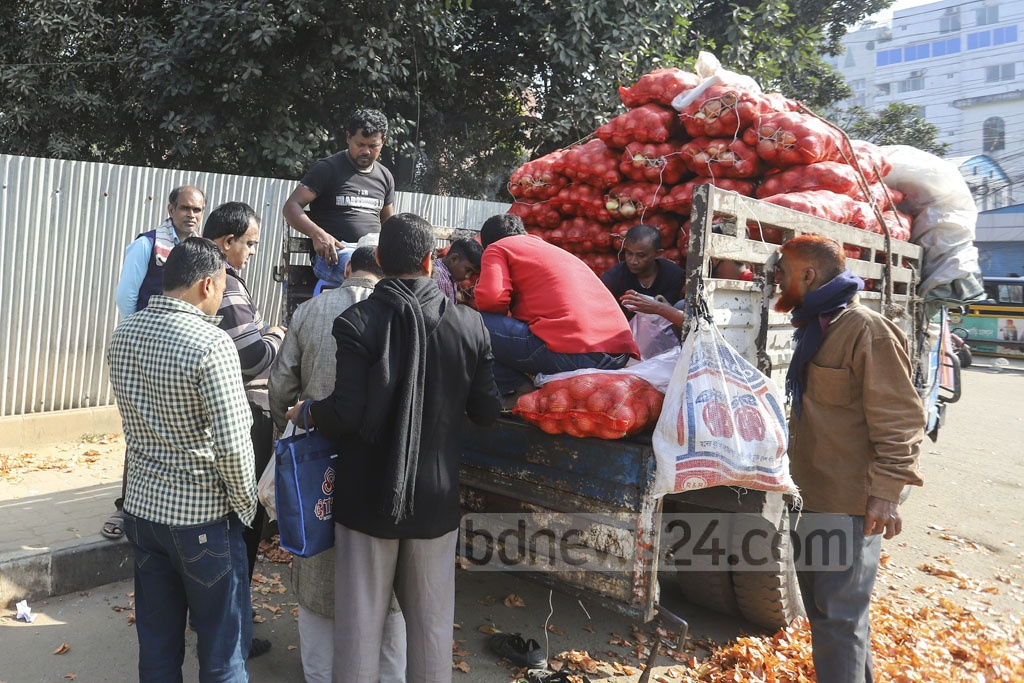 Dealers of the Trading Corporation of Bangladesh selling imported onion at Tk 35 per kg at Khamarbari intersection in Dhaka on Sunday but unlike previous weeks, there were not much crowds to buy the produces. Photo: Asif Mahmud Ove