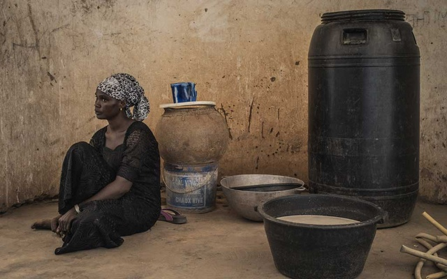 Khadijah Diagouraga rests after fetching water from a well near her home in the village of Koutia, Senegal, Jun 11, 2019. Wives are shocking their traditional West African villages by earning money and running large households while their husbands are in Europe seeking jobs. (Laura Boushnak/The New York Times).