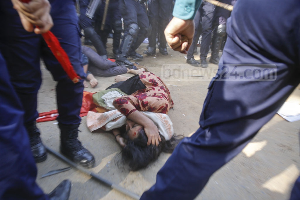 Two activists of the Left Democratic Alliance lie on the street after being injured in police beating at Matsya Bhaban intersection during an anti-government 'black flag' march in Dhaka on Monday. Photo: Mahmud Zaman Ovi