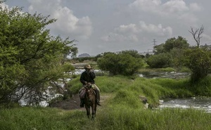 A cowboy rides near a tributary of the Santiago River contaminated with industrial and household waste in the town of El Salto, in Jalisco, Mexico, Sept 11, 2019. A. The New York Times