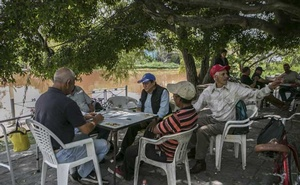 Men play dominoes in the shade along the Zula River near where it meets the Santiago River in the town of Ocotlán, in Jalisco, Mexico, Sept 11, 2019. The New York Times