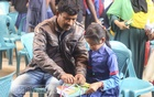 A man helping her excited daughter unpack the new textbooks at No. 1 Government Primary School in Munshiganj's Srinagar on Wednesday. The government distributed the books for free among millions of students throughout the country on the first day of the new year.