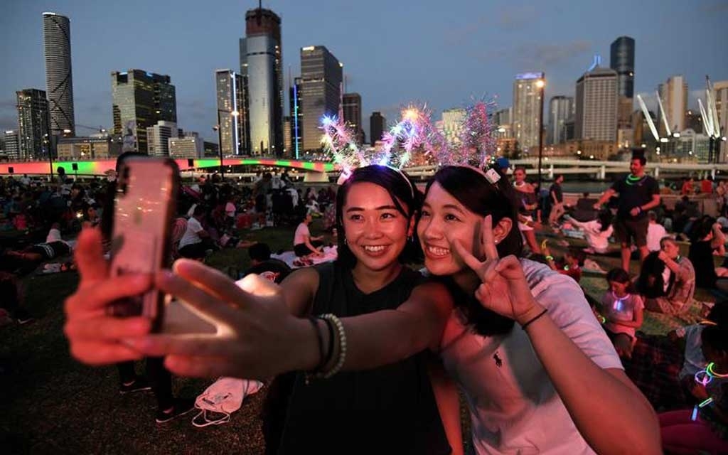 Mizuki (L) and Tsubasa take a selfie as they wait to watch the New Year's Eve fireworks at South Bank in Brisbane, Australia. AAP Image/Dan Peled/via REUTERS