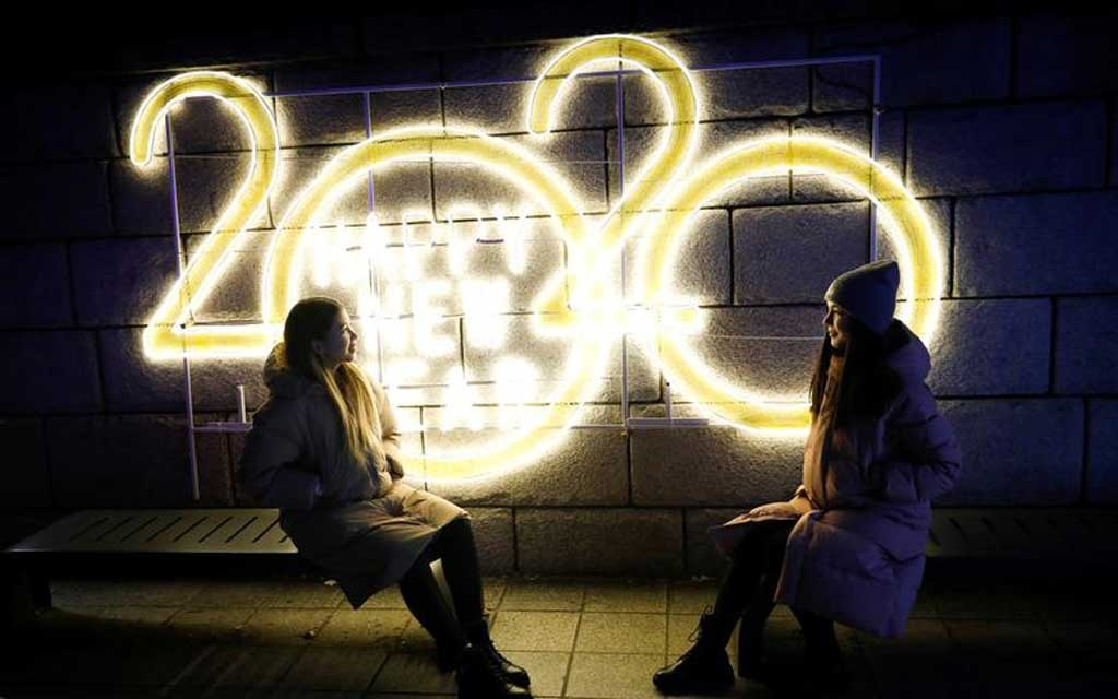 Women pose for a picture in front of a 2020 luminous sign during New Year s Eve in Seoul, South Korea. REUTERS