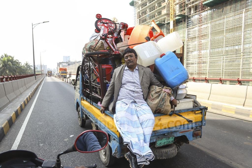 A man takes a risky ride on the back of a pickup packed with furniture and other things on Mayor Hanif Flyover in Dhaka while moving house on Wednesday.