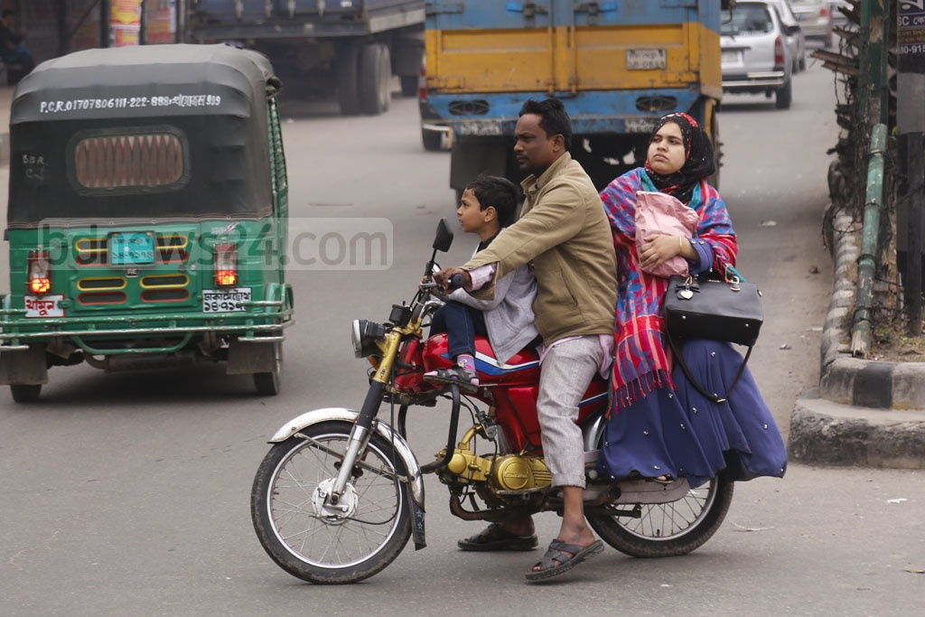 Three members of a family riding motorcycle without wearing helmets and putting their lives in danger at the capital's Atish Dipankar Road in Mugda. Photo: Mahmud Zaman Ovi