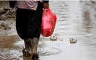 A woman carries a plastic bag containing food through the mud on a road after floods hit Bekasi, West Java province, Indonesia, Jan 3, 2020. REUTERS/Willy Kurniawan