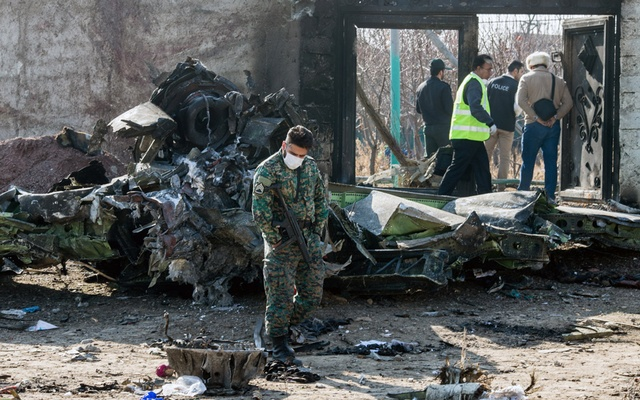 A security official examines a piece of wreckage at the site of the Ukraine International Airlines crash on the outskirts of Tehran on Wednesday, Jan. 8, 2020. A Ukrainian Boeing 737-800 carrying at least 170 people Wednesday crashed shortly after takeoff from Tehran, killing everyone on board, according to the Iranian state news media. (Arash Khamooshi/The New York Times)