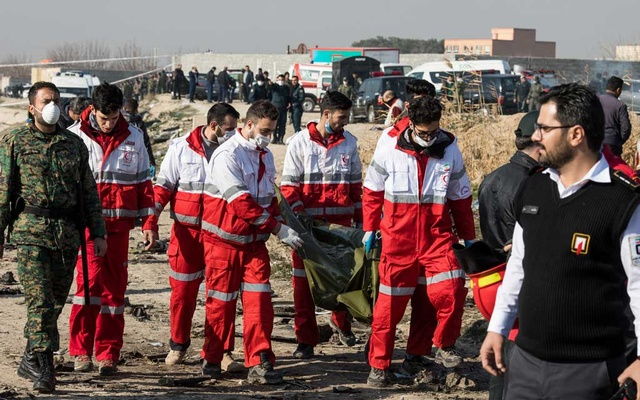 Rescue workers carry the remains of a victim at the site of the Ukraine International Airlines crash on the outskirts of Tehran on Jan 8, 2020