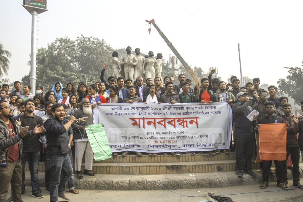 A group of Dhaka University teachers and students demonstrating at the altar of the Raju Memorial Sculpture on the campus on Monday demanding that the Election Commission changes Jan 30 as the voting day for Dhaka city because it coincides with Saraswati Puja.