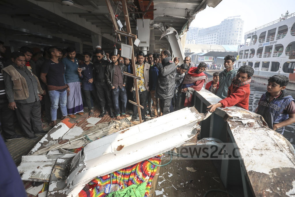 People gather to see the damaged parts of Kirtankhola-10 launch after a collission with another launch killed at least two people and injured 10 others in the Meghna river in the wee hours of Monday.
