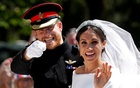 Britain's Prince Harry gestures next to his wife Meghan as they ride a horse-drawn carriage after their wedding ceremony at St George's Chapel in Windsor Castle in Windsor, Britain, May 19, 2018. REUTERS/FILE